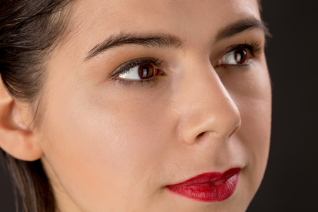 eyes hazel: A pretty woman with big red lips and hazel eyes and clean skin looking aside isolated on black background