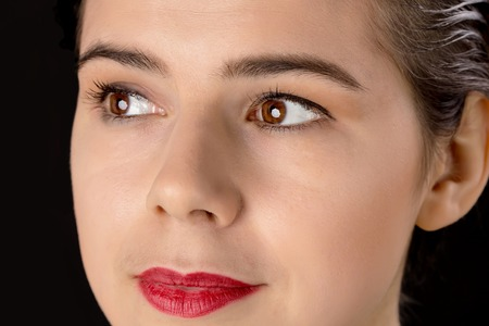 hazel eyes: A pretty woman with big red lips and hazel eyes and clean skin looking aside isolated on black background