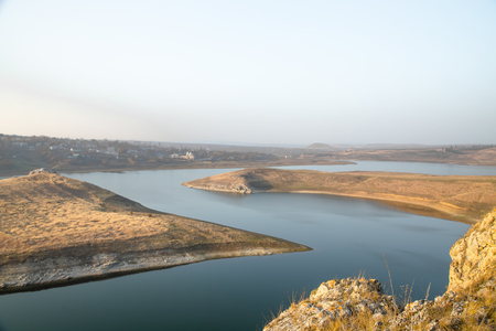 river banks: A panoramic view of beautiful river banks with grassy rocks and sky reflected in still waters Stock Photo