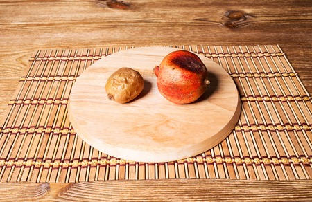 kiwi fruta: Spoiled pomegranate and kiwifruit on a round cutting board