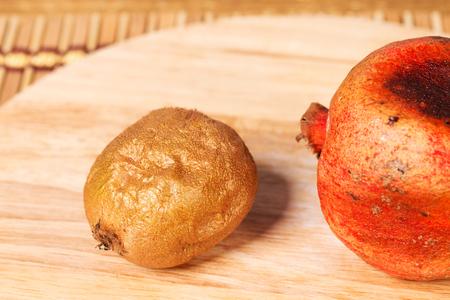 kiwi fruta: granada en mal estado y el kiwi en un tablero de corte redondo