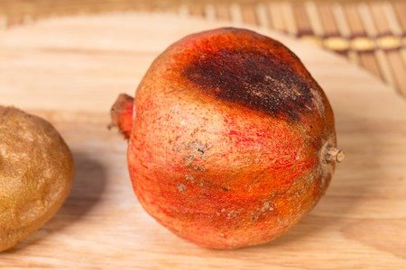 grenadine: Spoiled pomegranate and kiwifruit on a round cutting board