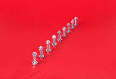 metal fastener: Steel bolts and nuts isolated on red background Stock Photo