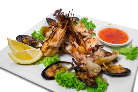 seafood platter: Delicious grilled seafood platter with hot sauce. Isolated on a white background. Stock Photo