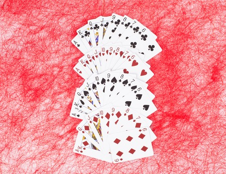 unpacked: New unpacked playing cards. Located on a red background. Stock Photo