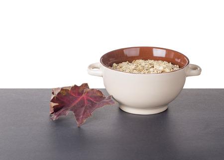 kasha: Oatmeal porridge in ceramic drinking bowl and autumn leaf. Located on black table.