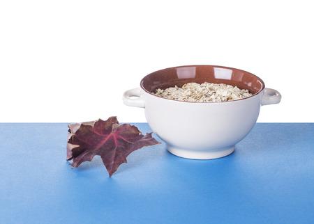 kasha: Oatmeal porridge in ceramic drinking bowl and autumn leaf. Located on blue table. Stock Photo