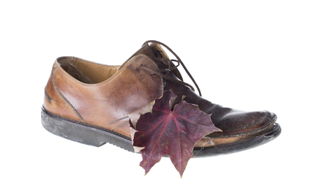 shoe string: Old shoes and autumn leaf. Isolated on the white background. Stock Photo