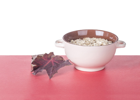 kasha: Oatmeal porridge in ceramic drinking bowl and autumn leaf. Located on red table.