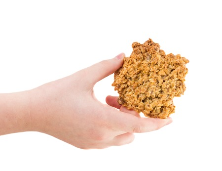 cereals holding hands: Hand holding delicious oatmeal cookie. Isolated on a white background. Stock Photo