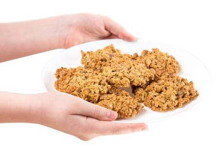 cereals holding hands: Hands holding plate with oatmeal biscuits. Isolated on a white background.