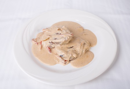 white canvas: Grilled meat covered with mushroom sauce. Plate located on a white canvas tablecloth background. Stock Photo