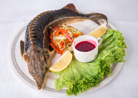 sturgeon: Baked sturgeon with vegetables and sweet red sauce. Plate located on a white canvas tablecloth background.