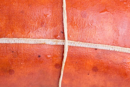 the casing: Closeup of smoked sausage casing with rope. Macro. Photo can be used as a whole background.