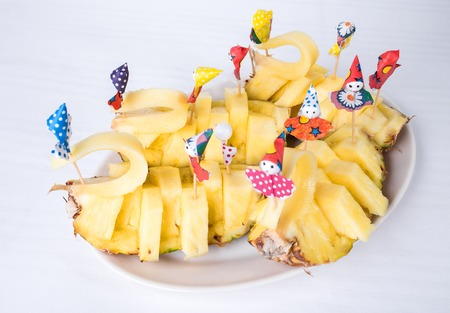 fruit plate: Delicious sliced pineapple with paper umbrellas. Plate located on a white canvas tablecloth background. Stock Photo