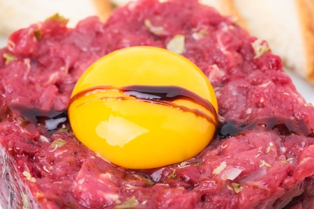 steak tartare: Delicious steak tartare covered with soya sauce with egg yolk and sauce. Macro. Photo can be used as a whole background.