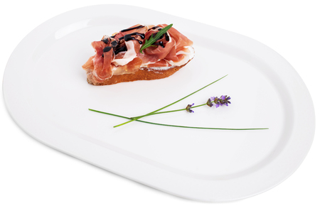 balsamic: Prosciutto bruschetta with ricotta and arugula covered with caramelized balsamic vinegar. Isolated on a white background. Stock Photo