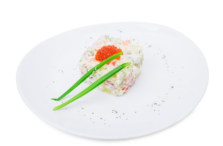 traditonal: Traditonal russian salad olivier with red salmon caviar and scallion. Isolated on a white background. Stock Photo