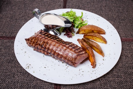 porterhouse: Delicious beef steak with roasted potatoes and fresh lettuce. Plate located on a brown tablecloth background. Stock Photo