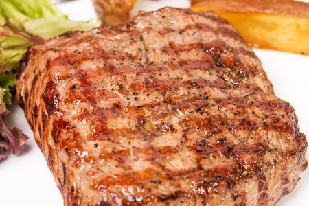 new york strip: Traditional New York strip steak with potato wedges and fresh lettuce. Macro. Photo can be used as a whole background.