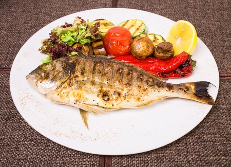 dorado fish: Grilled dorado fish with vegetables and sliced lemon. Plate located on a brown canvas tablecloth background.