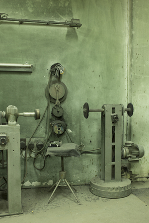 manufactory: Old manufactory. Grinding macines on the background of the old wall.