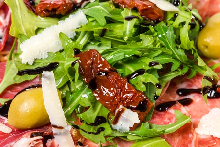 Italian salami and prosciutto platter with grated parmesan and fresh arugula covered with balsamic vinegar. Macro. Photo can be used as a whole background.