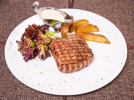 new york strip: Traditional New York strip steak with potato wedges and fresh lettuce. Plate located on a brown canvas tablecloth background. Stock Photo