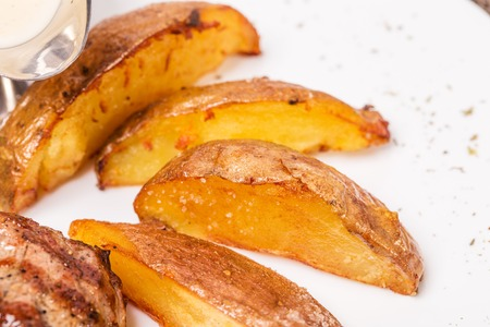 new york strip: Potato wedges as a garnish for new york strip steak. Macro. Photo can be used as a whole background. Stock Photo