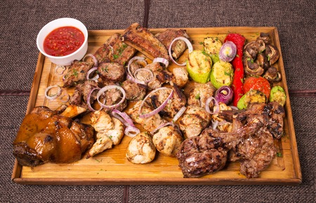 Mixed various grilled meat platter with vegetables and spicy tomato sauce. Located on a brown canvas tablecloth background. Imagens