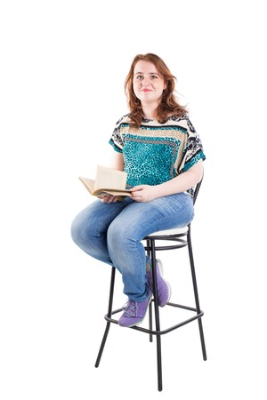 bar chair: Beautiful redhead plus size model with book sitting on the bar chair. Isolated on a white background.