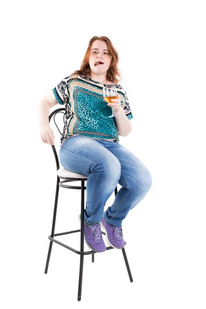 bar chair: Smiling redhead plus size wreckled model sitting on the bar chair with glass of whiskey and cigar. Studio shot. Isolated on a white background.