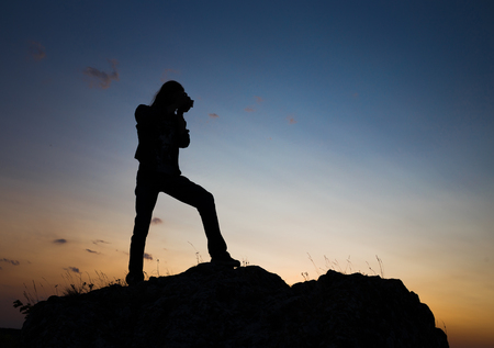 longhair: Silhouette of young longhair male model making photo shot with dslr camera at blue and yellow sunset. Stock Photo