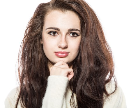 chin on hands: Portrait of smiling beautiful brunette model with freckles and long hair in yellow sweater. With hands on her chin. Isolated on a white background.