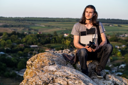 longhair: Handsome young longhair man sitting on a rocks with digital dslr camera against fields and blue background. Sunset shot.