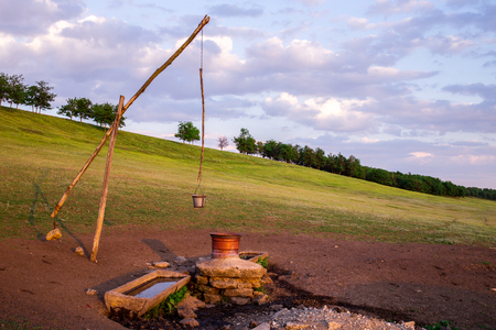 draw well: Beautiful shot of typical draw well near the fields. Sunset shot. Photo can be used as a whole background.