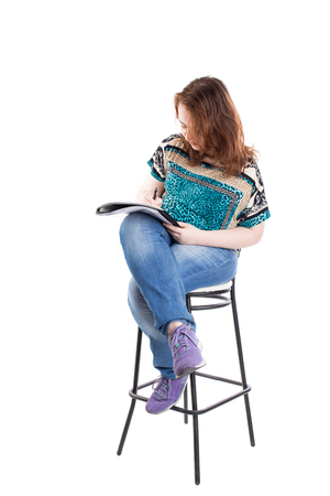 bar chair: Beautiful smiling redhead plus size wreckled model with folder and ballpoint pen sitting on the bar chair. Isolated on a white background.