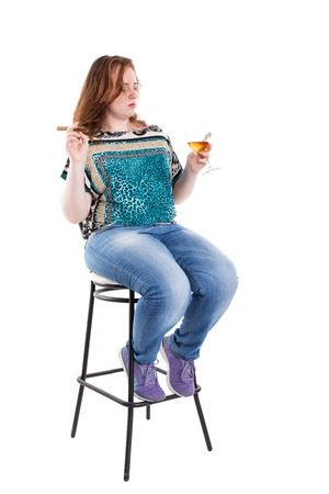 liquor girl: Smiling redhead plus size wreckled model sitting on the bar chair with glass of whiskey and cigar. Studio shot. Isolated on a white background.