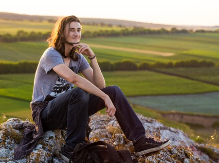 longhair: Handsome young longhair man sitting on a rocks against fields and blue background. Sunset shot. Stock Photo
