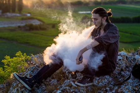 Handsome young man sitting on a rocks and smoking electronic cigarette at outdoors. Banco de Imagens