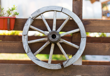 carreta madera: Old wooden wagon wheel on the fence.
