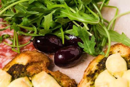 antipasto platter: Traditional tuscan antipasto platter with kalamata olives and fresh arugula. Macro. Photo can be used as a whole background.