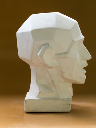 chins: Tutorial primitive plaster head model. Side view. Located against wall as a background.