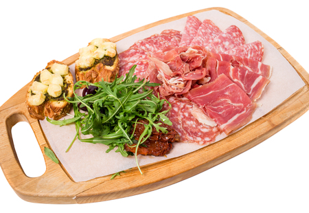antipasto platter: Traditional tuscan antipasto platter with cold cuts and dried tomatoes. Isolated on a white background.