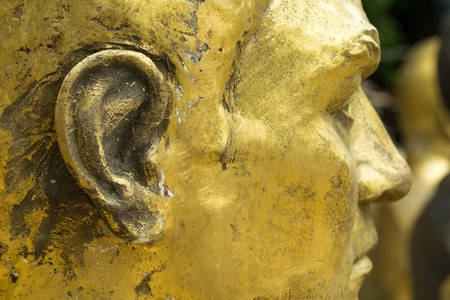 cheek: Closeup of unfinished bronze head. Focus on cheek and ear. Stock Photo