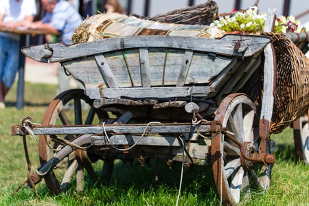 old wood farm wagon: Old wooden cart with flower pots and wicker baskets closeup at summer day. Photo can be used as a whole background.