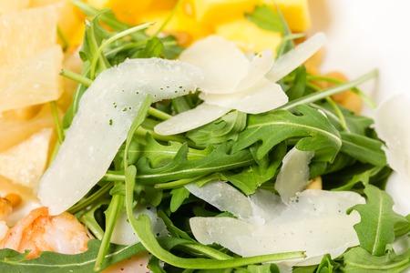 jumbo shrimp: Closeup of arugula and parmesan in jumbo shrimp salad with mango and avocado. MAcro. Photo can be used as a whole background. Stock Photo