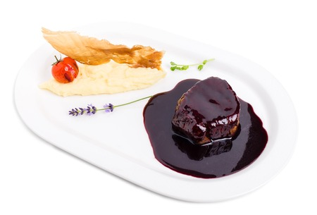 meta: Beef medallion in chianti sauce with potato puree and dried jamon. Isolated on a white background.