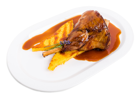 shank: Fried lamb shank with polenta and covered with red sauce. Isolated on a white background.