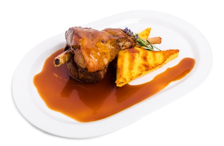 lamb shank: Fried lamb shank with polenta and covered with red sauce. Isolated on a white background.